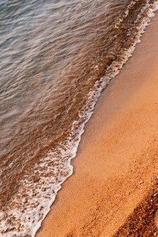 Les vagues de la mer courent sur le sable orange sur la plage