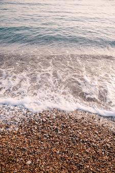 Vagues de la mer avec des galets orange sur la plage