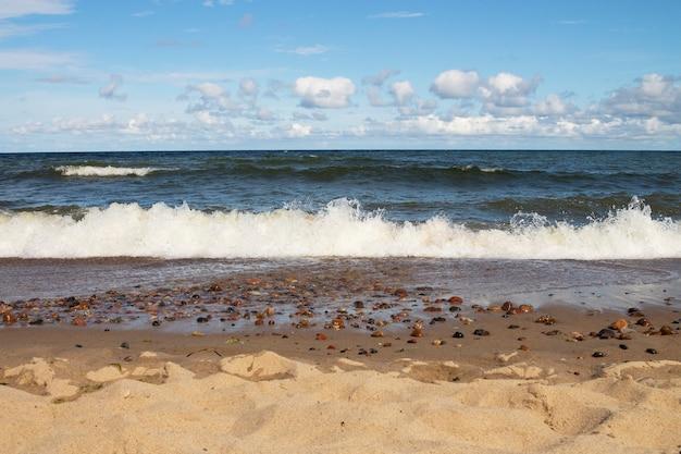 Vagues De La Mer Et Rochers Sur Le Rivage Sablonneux. Vacances En Mer, Marée Haute Photo Premium