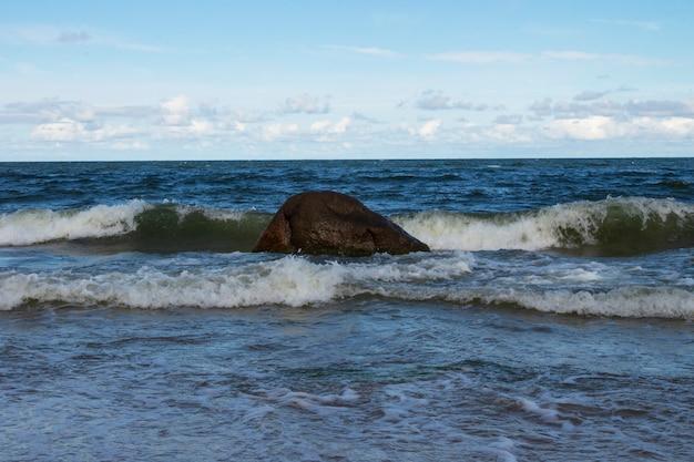 Vagues de la mer et rochers sur le rivage sablonneux. vacances en mer, marée haute