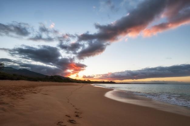Vagues de la mer s'écrasant sur le rivage pendant le coucher du soleil