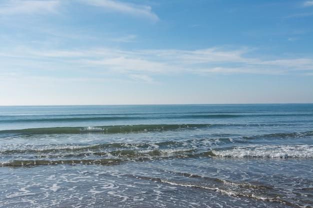Vagues, mer et soleil se reflétant sur la plage