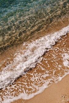 Vagues de la mer à la surface d'une plage de sable