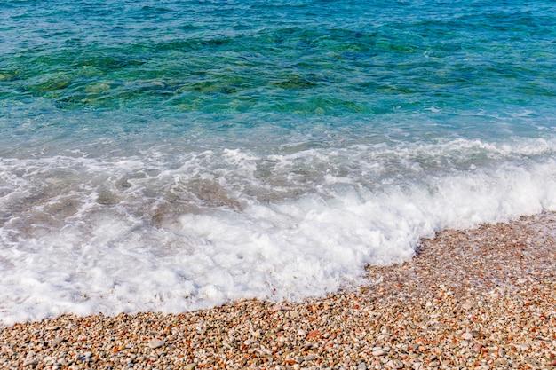 Vagues de la mer turquoise éclaboussant sur le rivage de galets