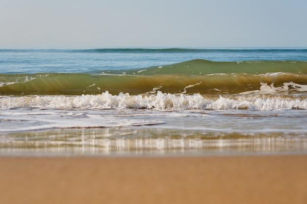 Vagues avec de la mousse sur une plage de sable.
