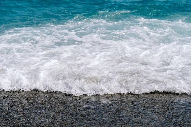 Vagues mousseuses blanches sur la plage de sable gros plan. bord de mer par une journée d'été ensoleillée. concept de temps de vacances d'été.