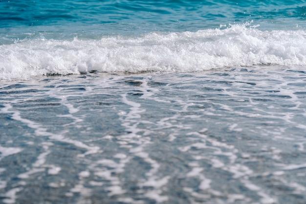 Vagues mousseuses blanches sur la plage de sable gros plan. bord de mer par une journée d'été ensoleillée.