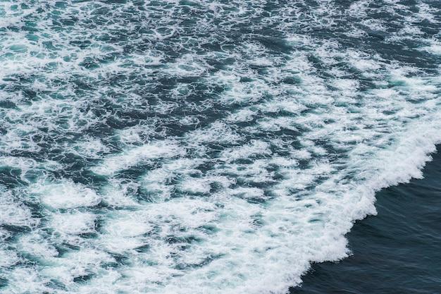 Vagues de l'océan blanc se brisant sur les rochers de la mer côtière en été.