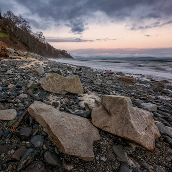 Vagues de l'océan s'écrasant sur la rive pendant le coucher du soleil