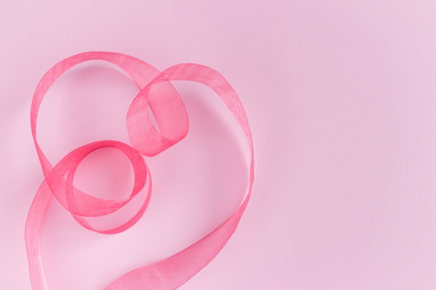 Vagues de ruban de soie de satin rose festif en forme de coeur sur fond rose. décoration de vacances. emballage actuel. copyspace pour le texte