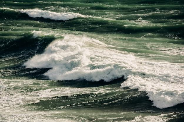 Vagues vertes de tempête dans la mer profonde. vagues déferlantes poussées par le vent sur l'eau de mer