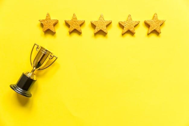 Vainqueur de conception simplement plat ou coupe du trophée d'or de champion et note de cinq étoiles isolée sur jaune