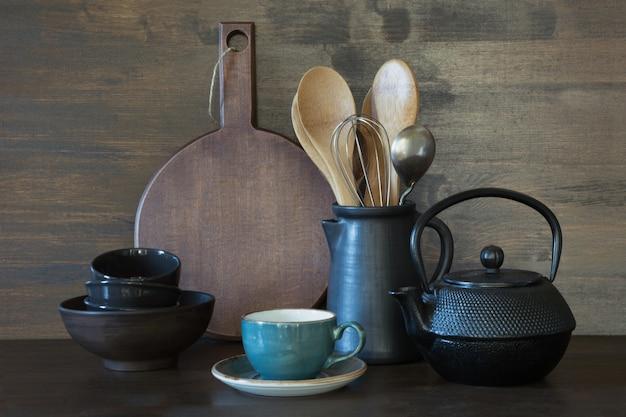Vaisselle, argile, ustensiles sombres et autres objets divers sur une table en bois.