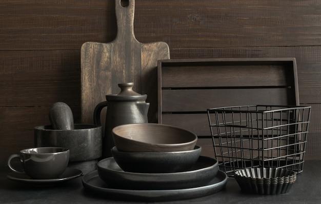Vaisselle, argile, ustensiles sombres et autres objets sur un plateau sombre