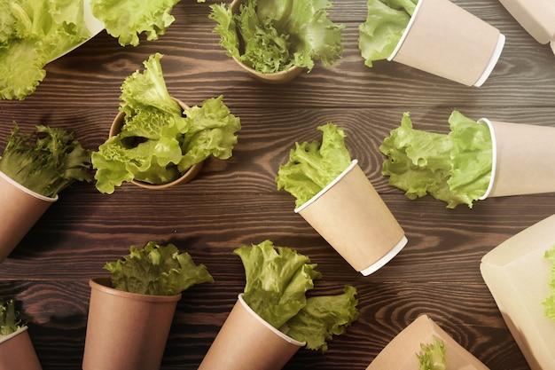 Vaisselle biodégradable et verts sur une surface en bois