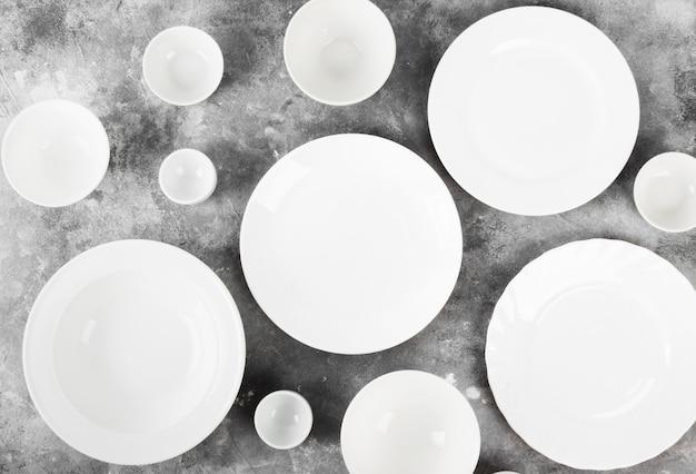 Vaisselle blanche propre sur fond gris. vue de dessus