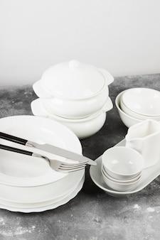 Vaisselle blanche propre sur fond gris.