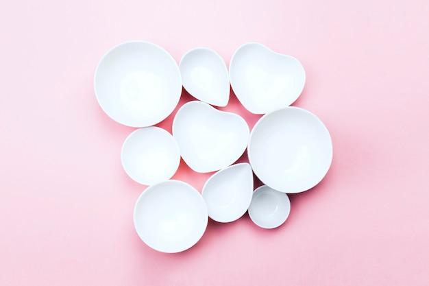 Vaisselle blanche propre sur fond rose. vue de dessus