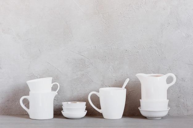 Vaisselle blanche sur la table contre le mur gris texturé