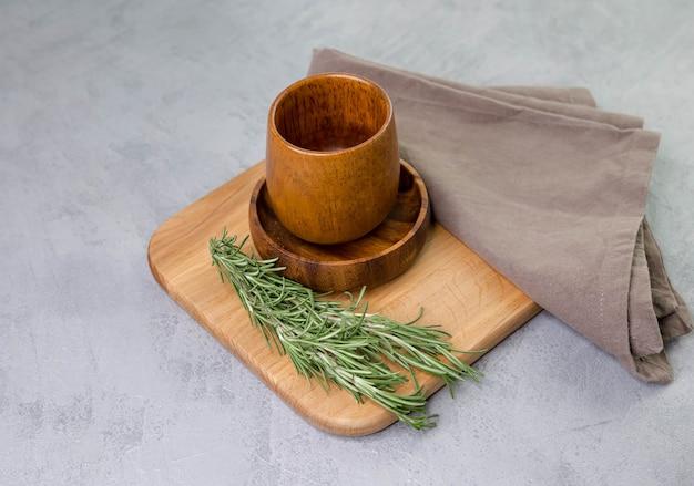 Vaisselle en bois écologique et plante sur fond de béton