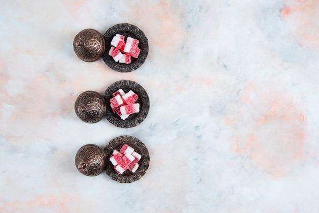 Vaisselle de bonbons d'affilée sur une surface blanche