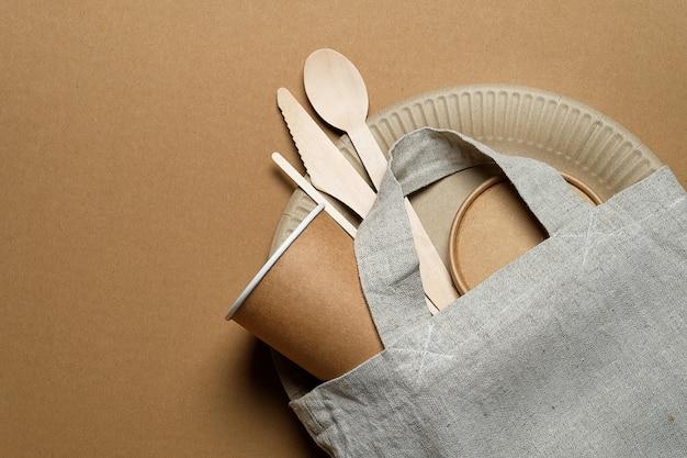 Vaisselle écologique jetable en bois de bambou et papier, sac réutilisable en ficelle sur un carton. la photo est couverte de grain et de bruit.