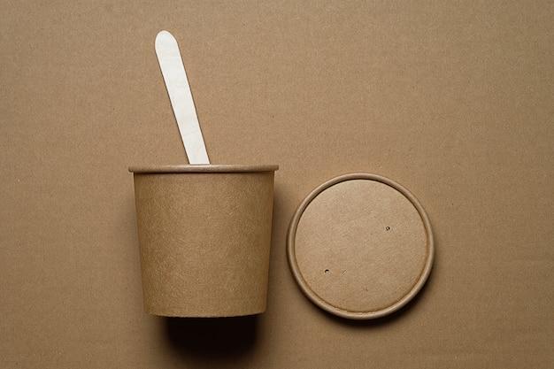 Vaisselle jetable en bois de bambou et papier sur beige. la photo est couverte de grain et de bruit.