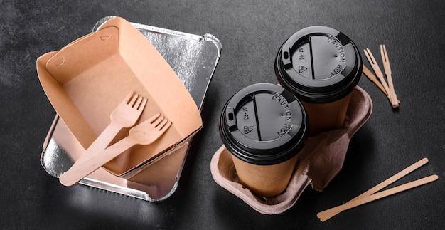 Vaisselle jetable en carton marron respectueux de l'environnement sur fond sombre. livraison de nourriture dans des plats jetables