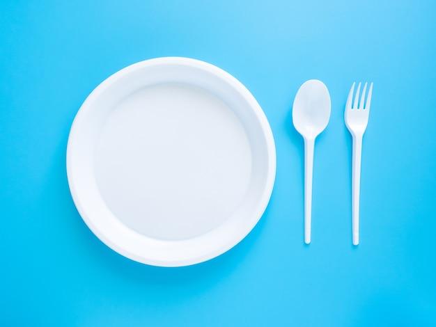 Vaisselle jetable, cuillères en plastique blanc, fourchettes, verres et assiettes isolés