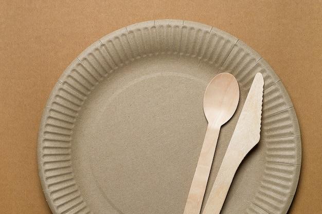 Vaisselle jetable écologique en bois de bambou et papier sur un carton. la photo est couverte de grain et de bruit.