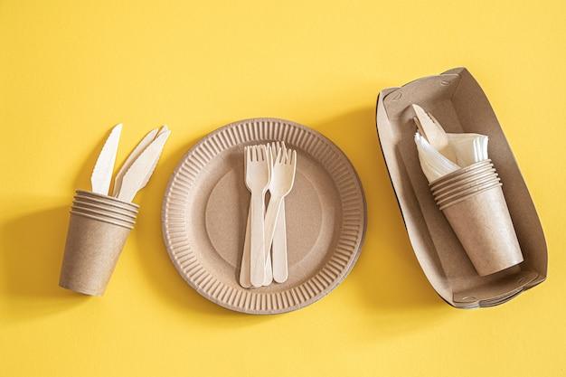 Vaisselle jetable écologique en papier sur fond orange.