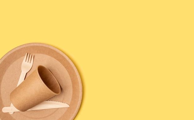 Vaisselle en papier jetable à partir d'une assiette à couteaux et d'une fourchette de pique-nique sur fond jaune.