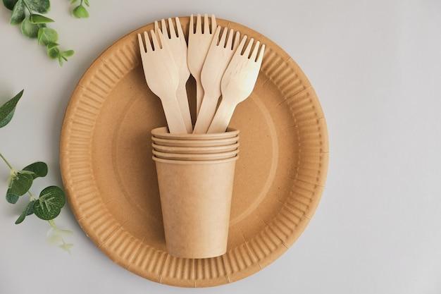 Vaisselle en papier kraft écologique sur une surface grise avec des feuilles vertes