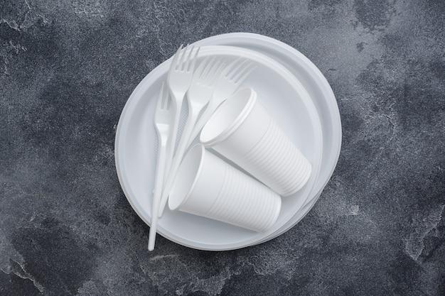 Vaisselle en plastique jetable sur une table sombre avec espace de copie.