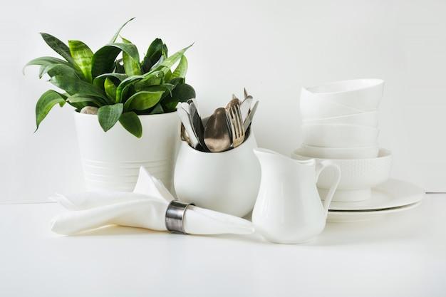 Vaisselle, plat, ustensiles et autres objets blancs sur un plateau blanc.