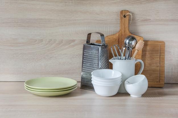 Vaisselle, vaisselle, ustensiles et autres objets divers sur un plateau en bois.