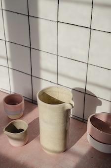 Vaisselle vide faite à la main telle que des pots en céramique, des tasses et des plats composés sur un carreau de cuisine blanc.
