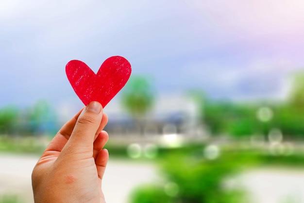 Valentin et concept, un coup de main avec un coeur rouge dans le ciel flou fond.