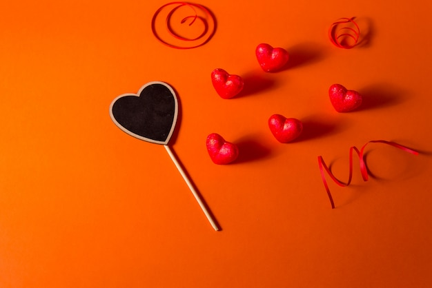 Valentin romantique abstrait coeurs en satin abstrait et fond de ruban. fond orange rouge avec coeurs