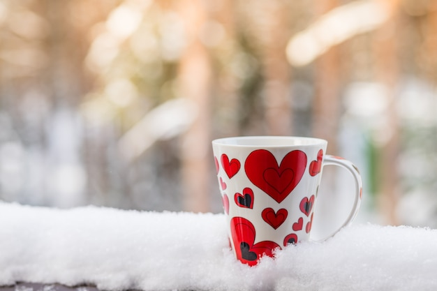 Valentin avec une tasse de café rouge sur fond blanc de neige, copie espace valentine concept.