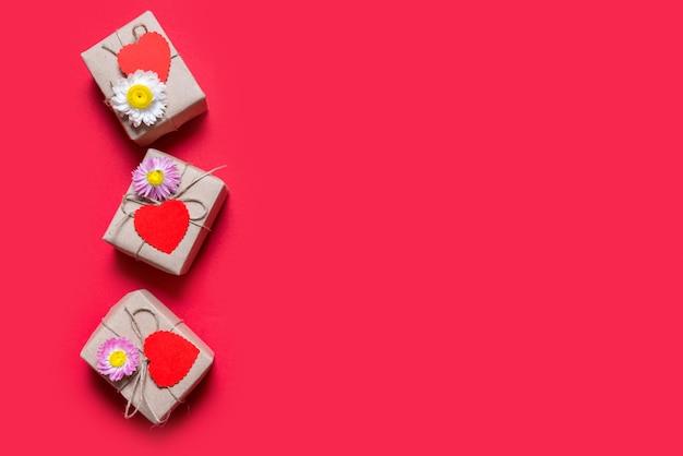 Valentin trois coffrets cadeaux sur fond rouge