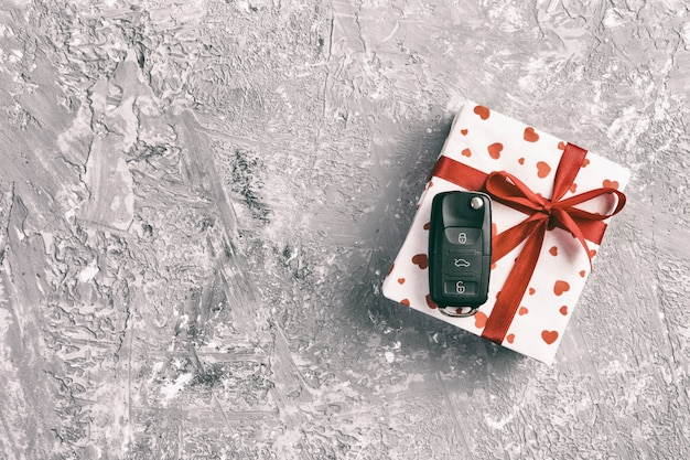 Valentine ou autre cadeau fait main de vacances en papier avec coeurs rouges, clés de voiture et boîte de cadeaux dans l'emballage de vacances. boîte de cadeau sur la vue de dessus de table de ciment gris avec espace de copie, un espace vide pour la conception