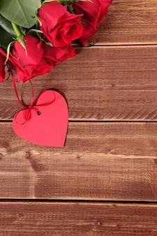 Valentine étiquette de cadeau et de roses rouges sur planche de bois