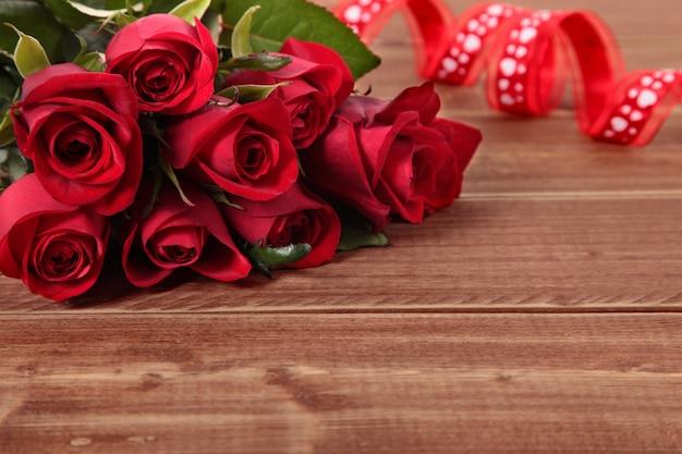Valentine roses rouges et ruban sur planche de bois