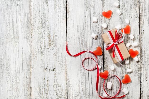 Valentines day candy coeurs guimauves et boîte de cadeaux en papier craft sur fond en bois blanc.