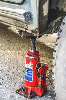 Un valet rouge soulève la voiture pour remplacer la roue crevée.