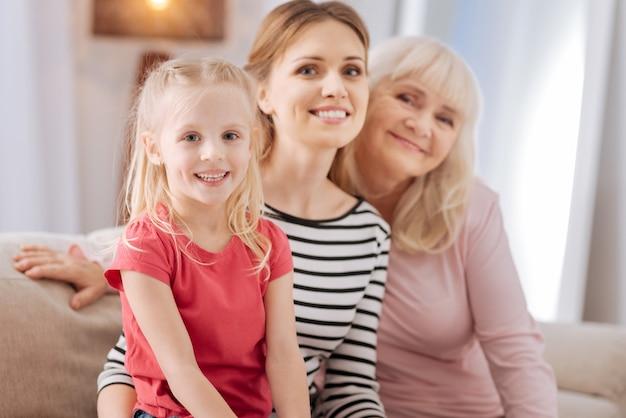 Valeurs familiales. heureuse jolie fille mignonne assise avec sa famille et souriant tout en vous regardant