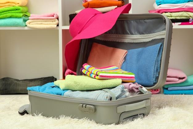Valise argentée ouverte avec des vêtements dans la chambre
