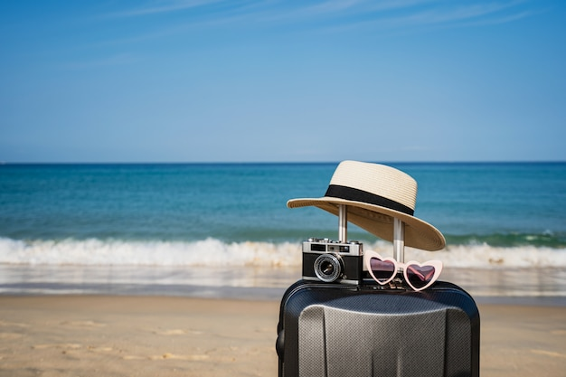Valise avec des articles de voyage sur la plage tropicale avec espace copie, concept de vacances d'été