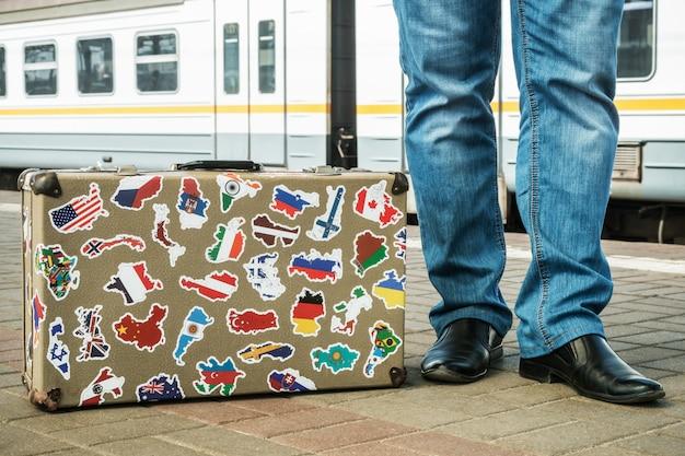 Une valise avec des autocollants du monde entier se dresse sur la plate-forme
